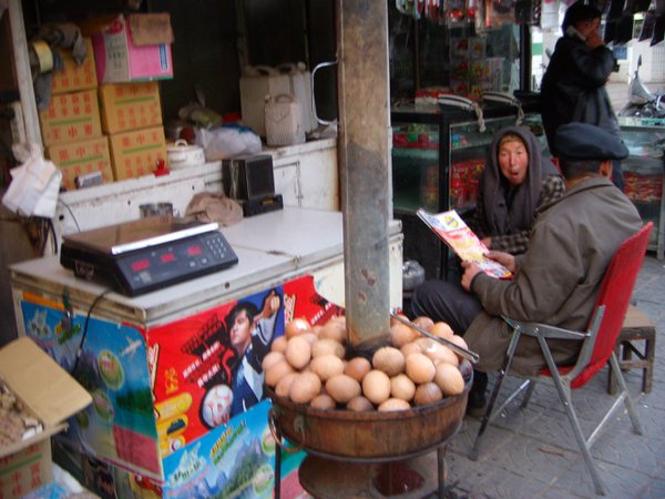 An elderly Uighur woman sells baked eggs. thumbnail