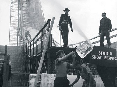Men feed blocks of ice into a snow machine in the Los Angeles Memorial Coliseum in 1938.