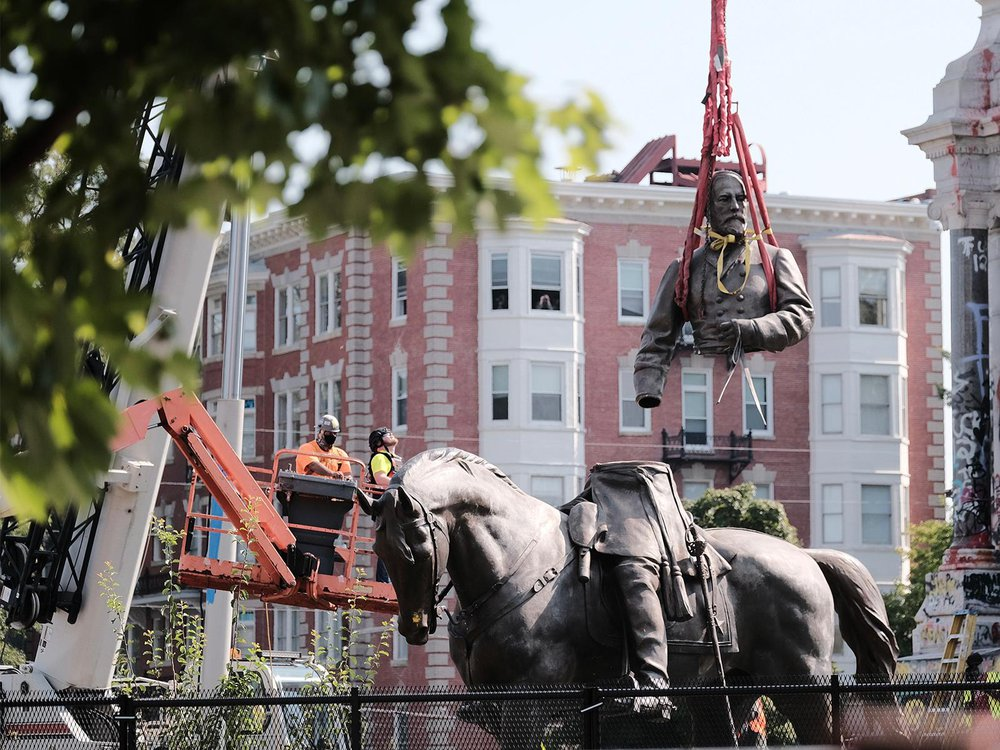A view of a crane lifting the top of the sculpture, including Lee's torso and arms, off of his legs and horse below