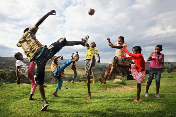 In Lesotho, a group of children play with their home made soccer ball, and spontaneously jump into the air to compete for the ball. Taken with a Nikon D700. thumbnail