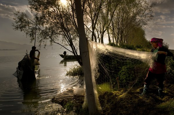 In the early morning, fishermen are cleaning their nets just outsight de town of Dali (China) on Erhai lake. thumbnail