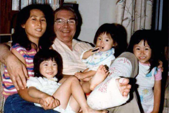 Old family photo  of mother and father and three young kids. The father has a cast on his leg, but all are smiling.