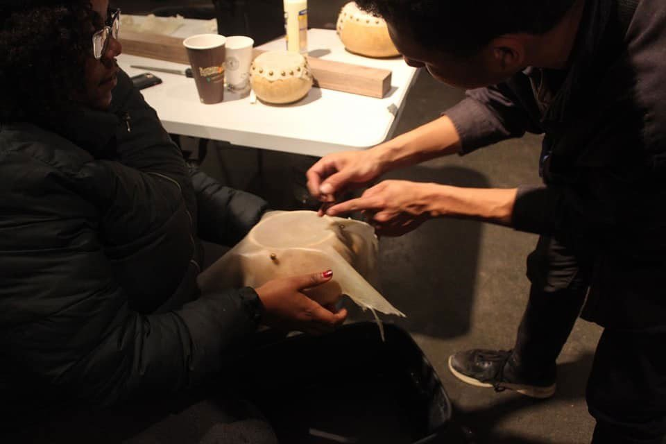 One person holds an animal skin over a hollowed gourd while another leans over to secure the skin.