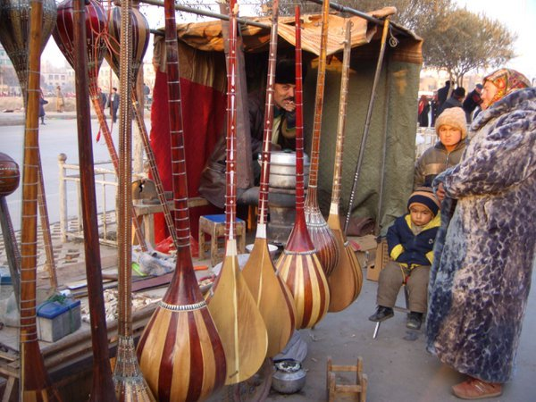 A woman dons a fabulous purple fur coat at a dotar stand in the oldest bazaar in the world in Kashgar, Xinjiang, China. thumbnail