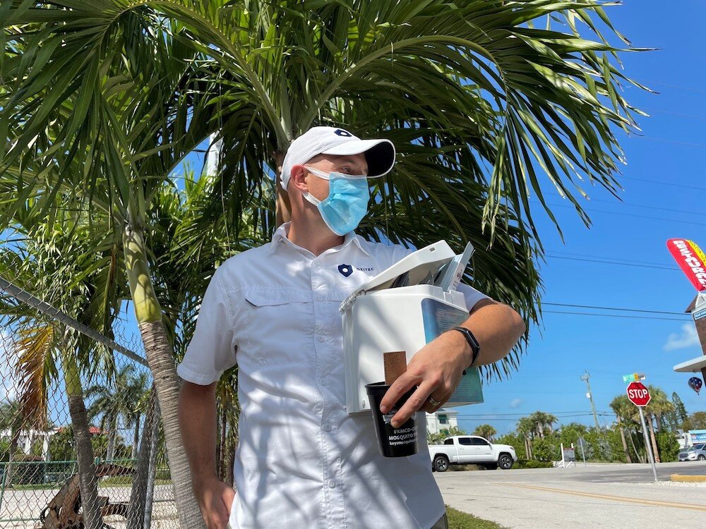 A man wearing a blue mask and a white baseball cap stands in front of a palm tree and holds a hexagon-shaped, toaster-sized box and a black cup