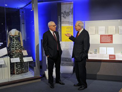 """David Rubenstein of The Carlyle Group and Warren Buffett of Berkshire Hathaway preview the """"Giving in America"""" display at the National Museum of American History."""