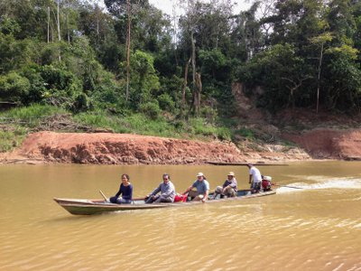 Paleontologists crossing the Rio Yurúa in Amazonian Perú, with the Santa Rosa fossil site in the background.