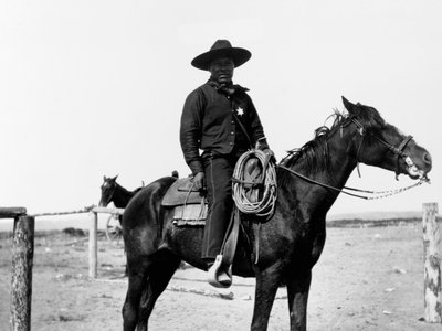 An African-American cowboy sits saddled on his horse in Pocatello, Idaho in 1903.