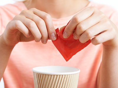 A woman adds artificial sweetener to a drink. The paranoia over the health dangers of aspartame can be traced back to an early Internet hoax.