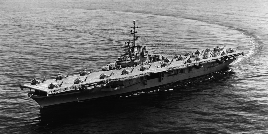 A black-and-white photo of a small aircraft carrier making a sweeping turn on a calm sea.