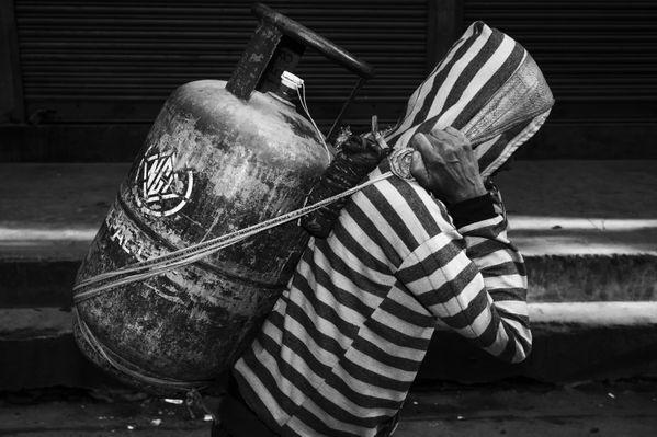 Nepali Man carries a gas tank thumbnail