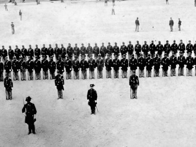Company H of the 48th New York Regiment, stiffly posed for this 1863 formal portrait at Fort Pulaski, in Savannah, GA, seems oblivious to the more informal baseball game in progress behind them.  The photo is one of the ealiest known photographs of a baseball game.