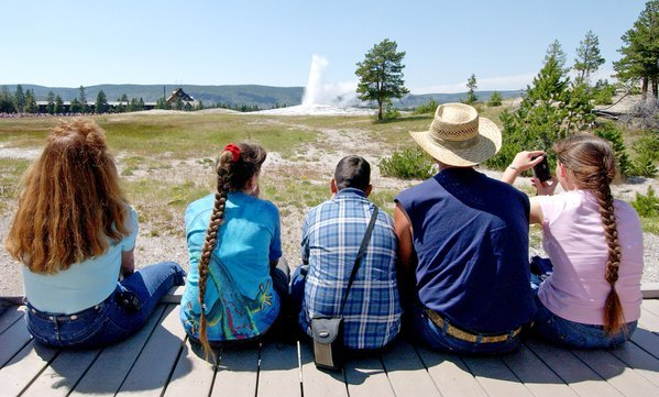 "Family watching ""Ol' Faithful"" erupt in Yellowstone National Park, WY. thumbnail"