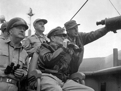 Brigadier General Courtney Whitney, government section, Far East Command; General Douglas MacArthur, Commander-in-Chief, United Nations Command, and Major General Edward Almond (at right, pointing), Commanding General, X Corps in Korea, observe the shelling of Incheon from the USS Mount McKinley.