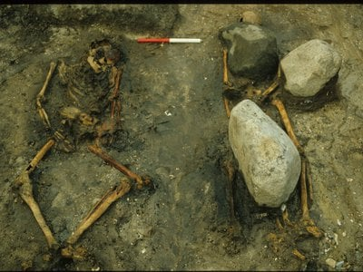 The male skeleton's neck and legs were arranged in an unnatural position, while the woman's remains were held in place by large stones.