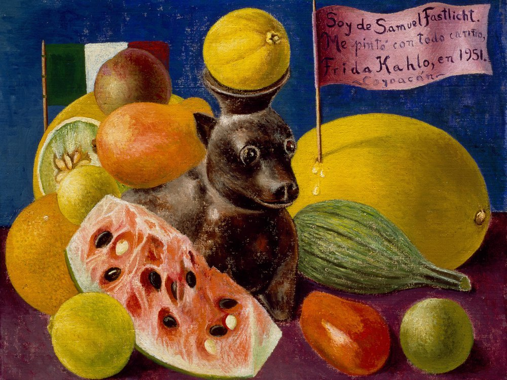 A still life with a small dog-shaped vessel in the center, holding a yellow fruit on its head; surrounded by watermelon cut open, other colorful fruits, a blue background and a flag with a phrase Soy de Samuel Fastlicht