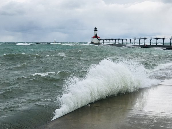 Wave crashing onto pier by lighthouse thumbnail