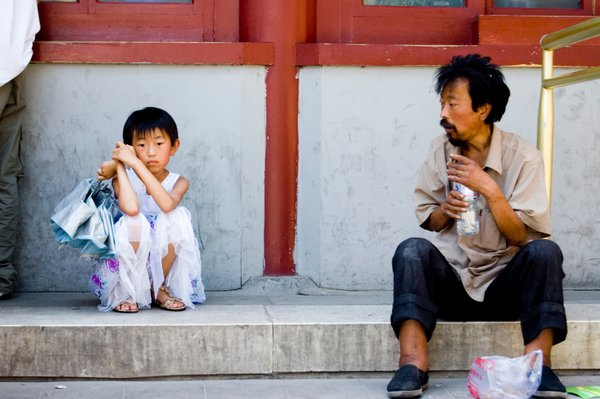 A young girl sits next to a homeless man outside the Forbidden city. thumbnail