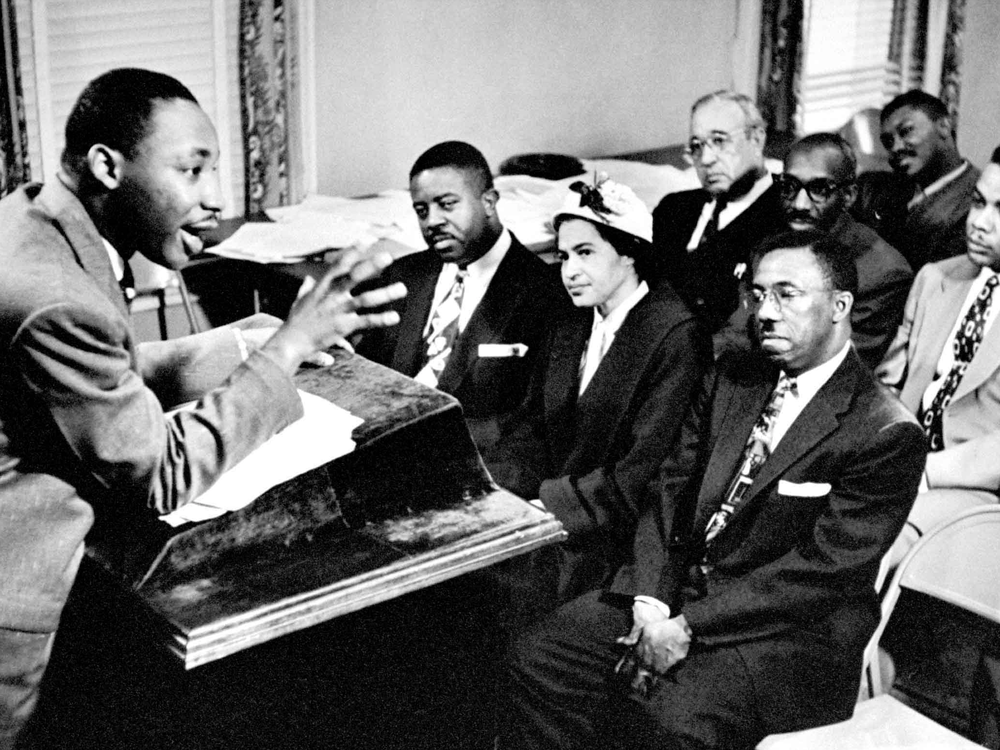 MLK Jr stands at a podium and speaks animatedly to a group of seven other people in chairs, including Rosa Parks and Ralph Abernathy, who all sit facing him