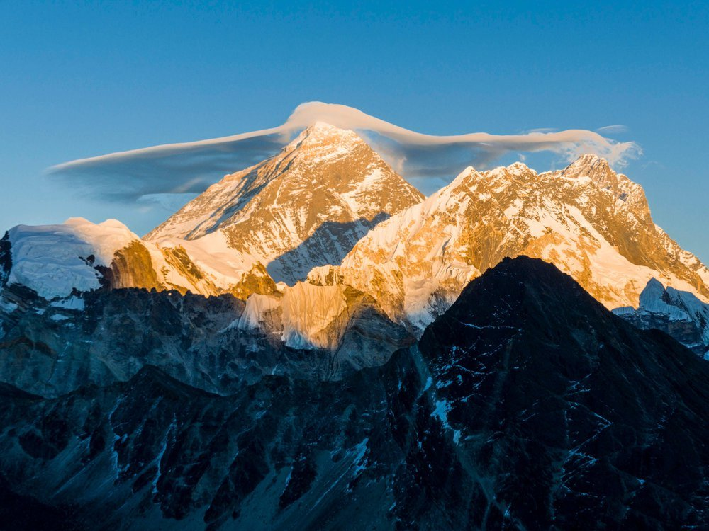 A landscape photograph of Mount Everest. The bottom half of the mountain is in the shade, but the sun warms the top half. Its peaks and valleys are covered with snow, and gray rocks emerge from beneath. The sky is bright blue and has a small white cloud.