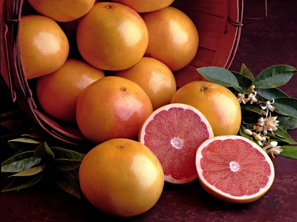 A stock image of a basket of grapefruit, a grapefruit sliced in half sits in the foreground