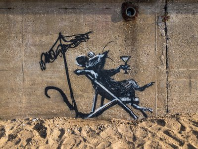 A vandal covered this mural of a rat sipping a cocktail in white spray paint.