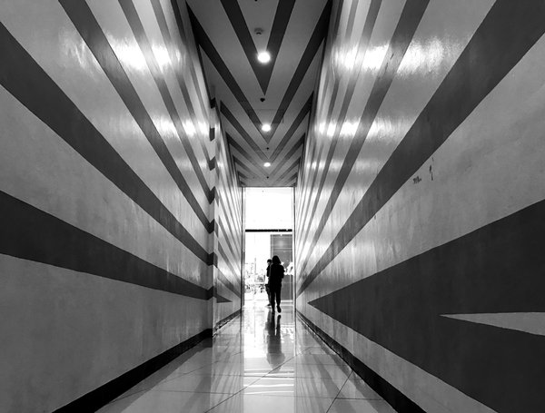 A lady at the end of a hallway with stripes on the wall thumbnail