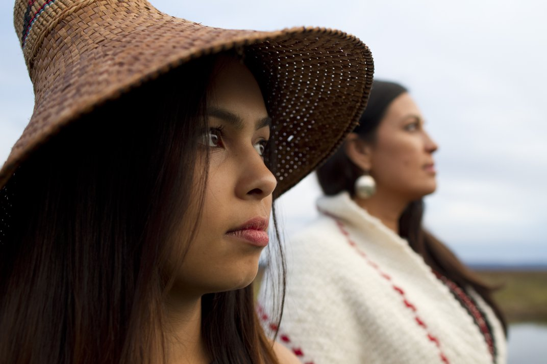 A close-up of a woman in a hat. Another woman in a white sweater stands behind her.