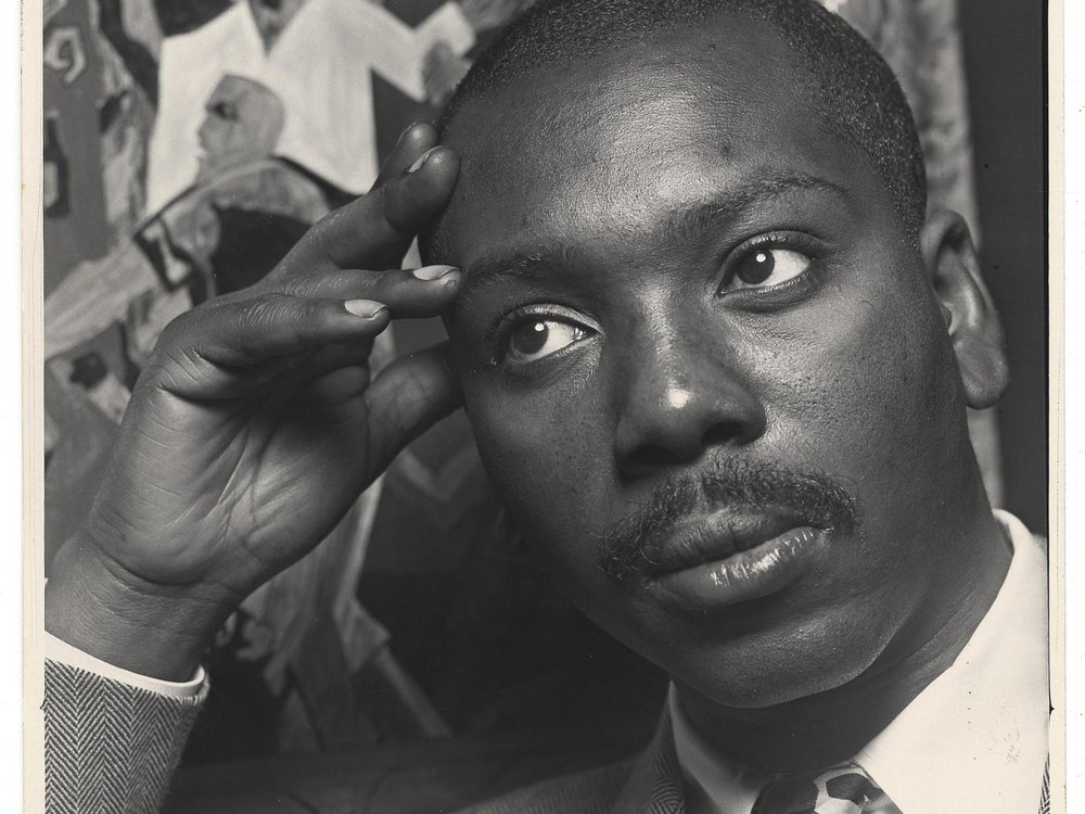 A black and white image of Lawrence, a black man with a mustache, looking contemplative with a suit and tie and resting his head against his hand, in front of one of his works of art