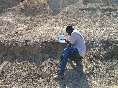 Sylvester Musembi Musyoka, a Kenyan colleague and field crew leader, recording a large mammal fossil bone during a virtual field project to collect fossils in Kenyan excavation sites that were in danger of being damaged by severe weather.