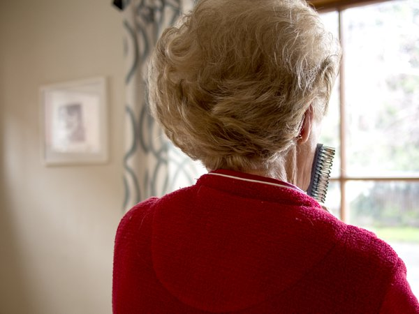 Grandmother standing in front of large window looking out. thumbnail
