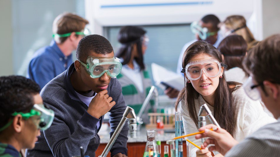 Young adult students of various ethnic backgrounds doing a chemistry experiment in class. The students are all wearing protective safety goggles.