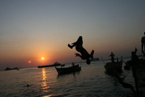 Frolicking boys leaping into the Indian Ocean at sunset. thumbnail