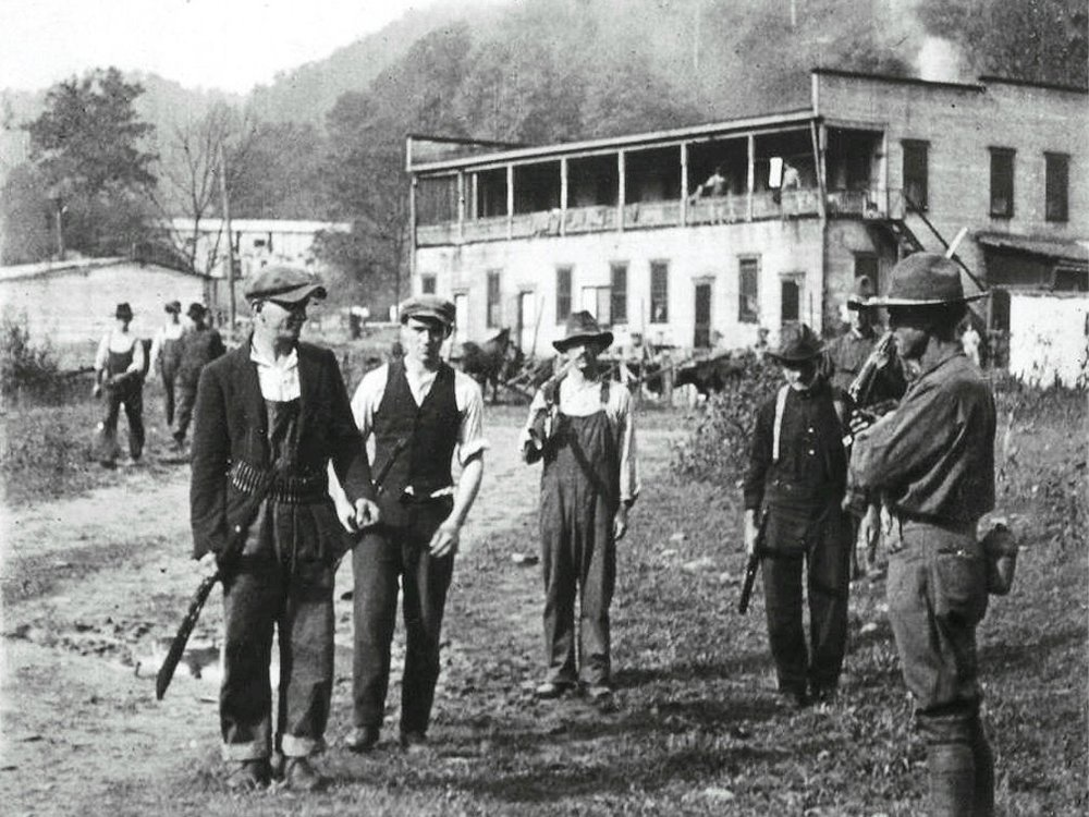 Three miners with federal soldier prepare to surrender weapons.
