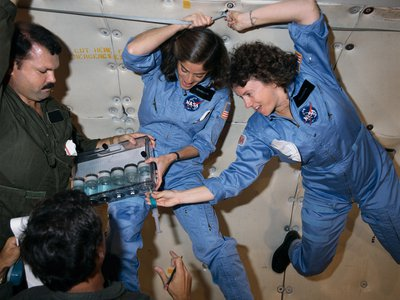 NASA Teacher-in-Space trainee Sharon Christa McAuliffe (right) and backup Barbara R. Morgan practice experiments during a zero-gravity training flight on October 16, 1985.
