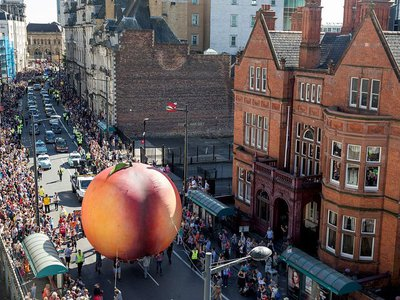 People gathered to watch a giant peach as it is moved through the center of Cardiff in September 2016—part of a celebration of the 100th anniversary of Roald Dahl's birth.