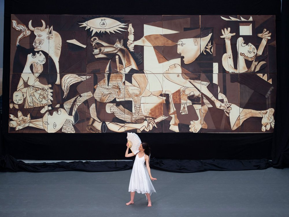 A person in a white flowy dress and holding a white fan dances in front of the enormous chocolate replica of Picasso's Guernica