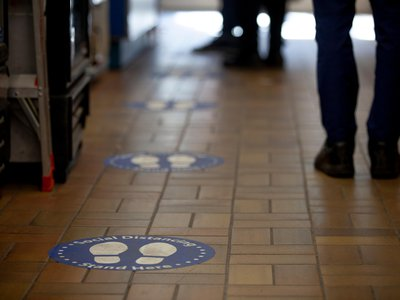 Signs on the floor encourage social distancing.