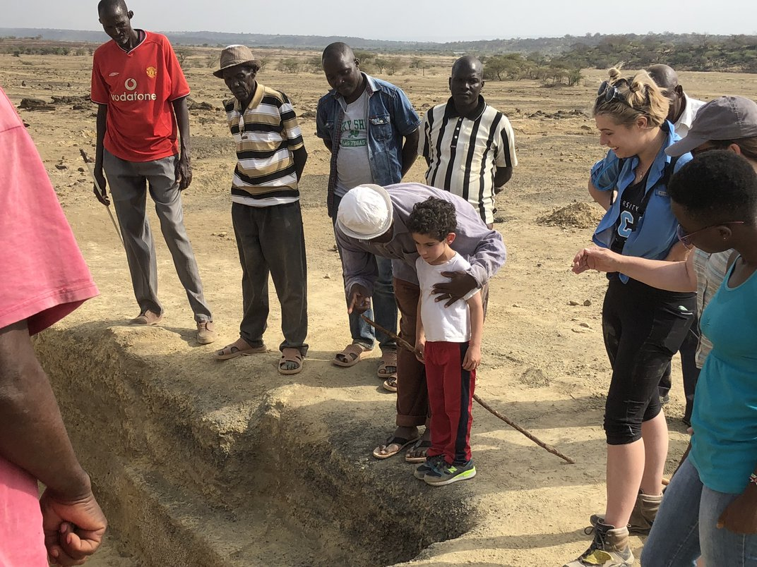 A young boy surrounded by a group of adults in a dry, brown desert in Kenya.