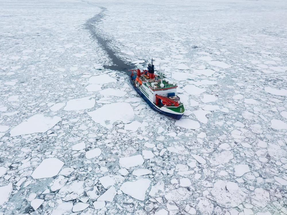 A photograph shows a white and red ship sailing through cracked sea ice