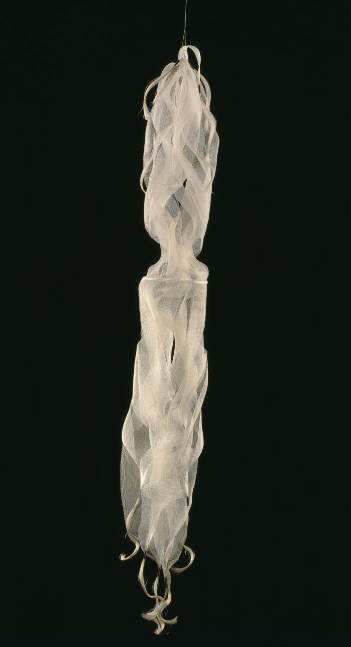 A white, hanging fiber sculpture against a black background