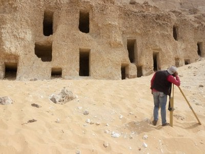 The rock-cut tombs are carved into different levels of a mountain face at the site.