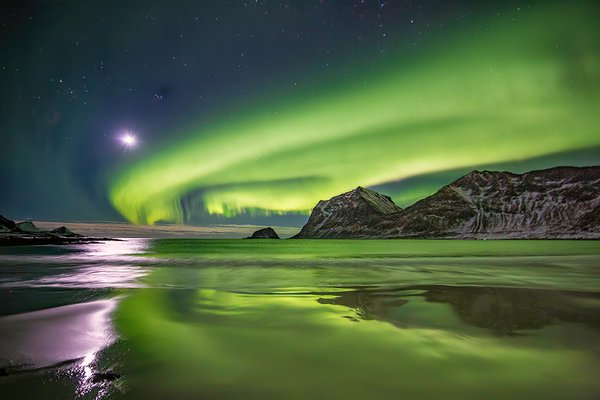 this is a photograph of a northern lights display with a close to a full moon in Norway, new Lofoten.