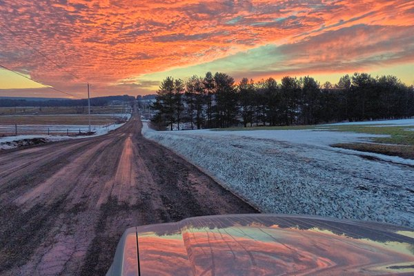 Red sunrise reflected on car hood thumbnail