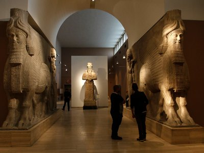 People look at ancient Assyrian human-headed winged bull statues at the Iraqi National Museum in Baghdad March 8, 2015.