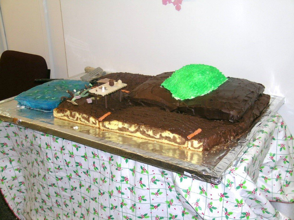 Brown and green chocolate longhouse made in the style of the Haida Native American tribe on a table with a white tablecloth with holly leaves.