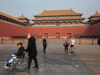 People walk past closed entrance of the Forbidden City in Beijing.