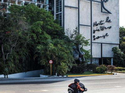 Ernesto Guevara cruises by an image of his father on a building in Havana's Plaza of the Revolution, one of the larges public squares in the world.