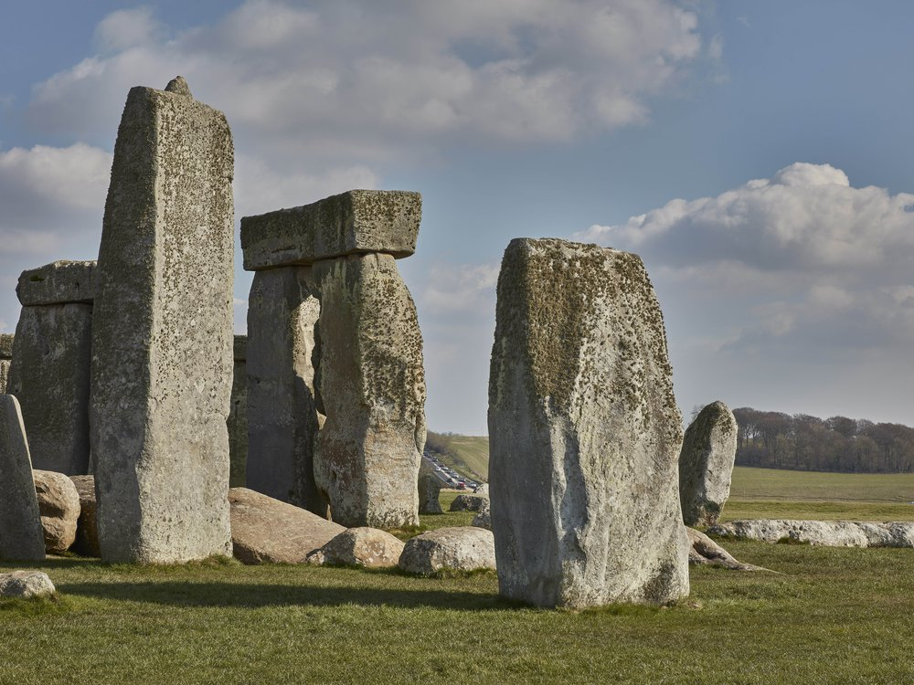 A view of Stonehenge's iconic square stones, under a blue sky with puffy white clouds; in the distance between two of the large stones, a trafficked road full of cars snakes over a hill