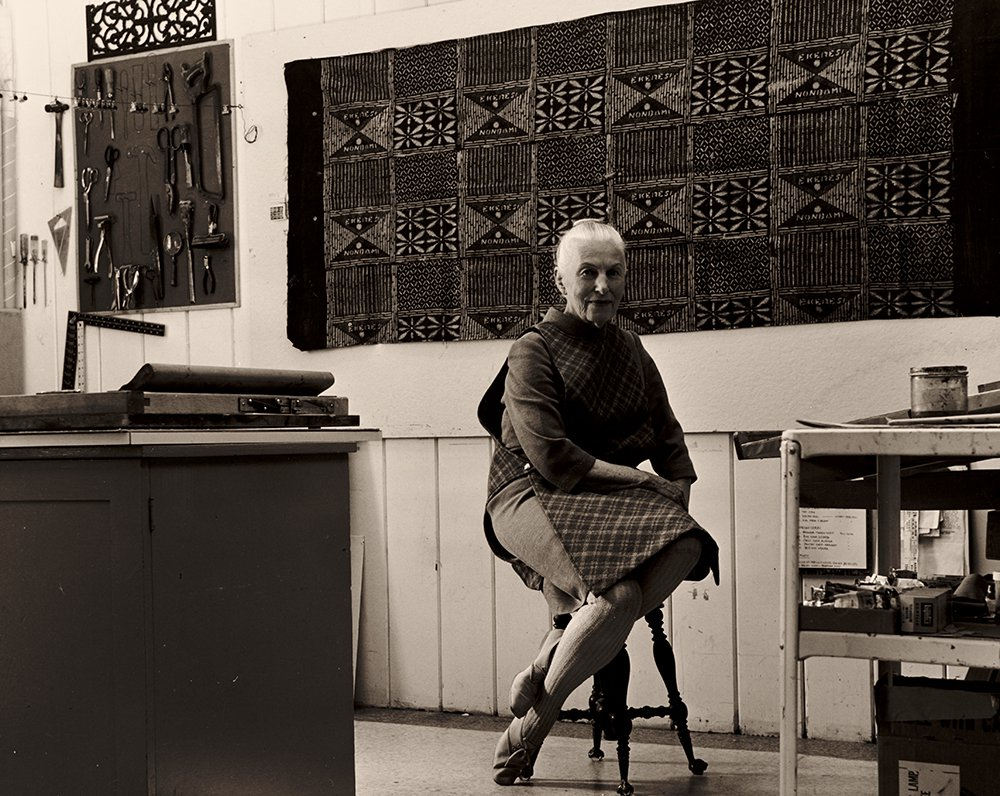 Photograph of Dorr Bothwell photographed in her studio surrounded by tools and textiles.